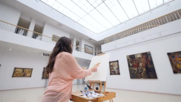 Női divat művész rajz egy képet a festőállvány. 4k