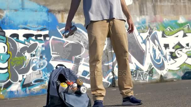 Mužské graffiti umělec vyvolá malířskou pikslu mezi rukama.
