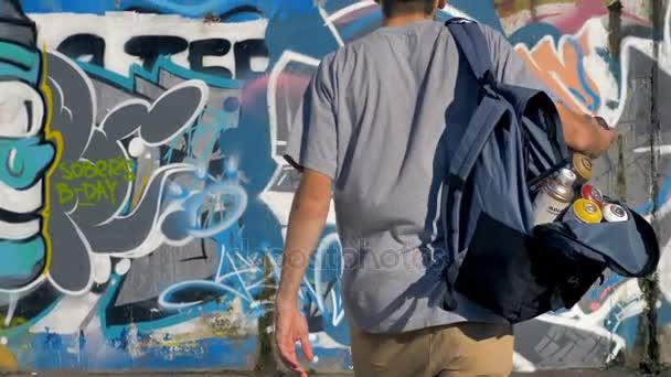 Egy férfi graffiti művész egy másik spray festék hozzáadása a graffiti fal.