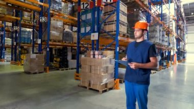 A warehouse employee looks around different aisles.