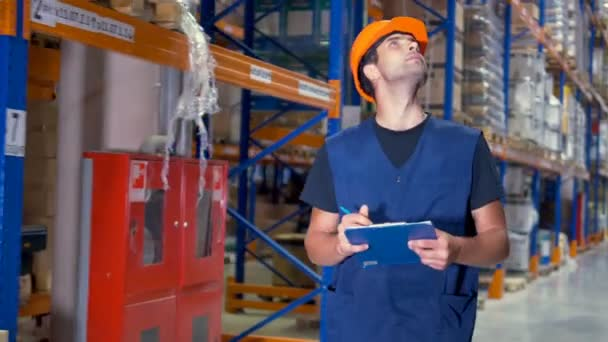 A male warehouse inspector makes clipboard notes while turning corners. 4K.