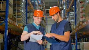 Two workers compare data at a warehouse.