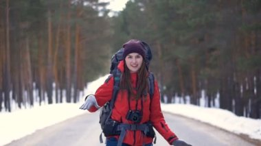 Happy tourist starting her trip, running along the road ina sunny winter forest. HD.