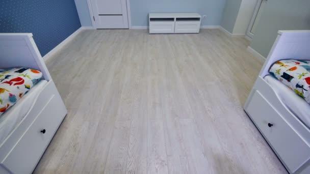 ein halb leeres Kinderzimmer, das schnell von einem Staubsaugerroboter gereinigt wird.