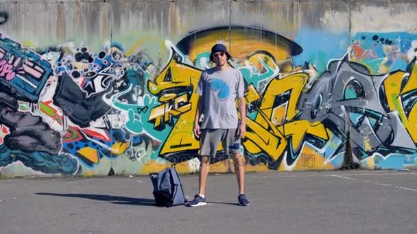 Graffiti umělec stojí stále poblíž jeho práce.