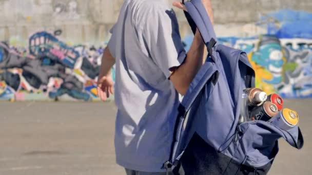 Graffitist klade na otevřený batoh plný plechovky od barev.