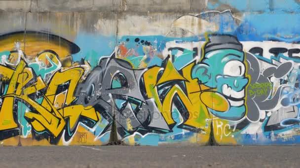 Vícebarevné graffiti pokrývá celé délce ulice zdi