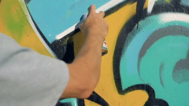 Egy kéz repaints graffiti a falon.