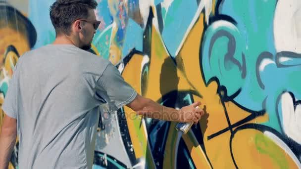 Egy férfi előadó repaints egy régi graffiti fal.
