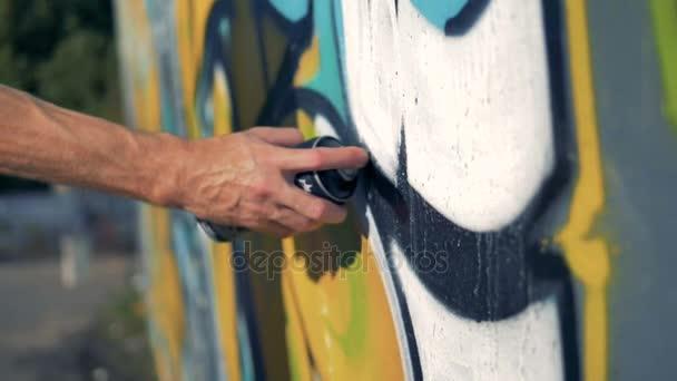 Ruka dělá černé čáry s graffiti malby.