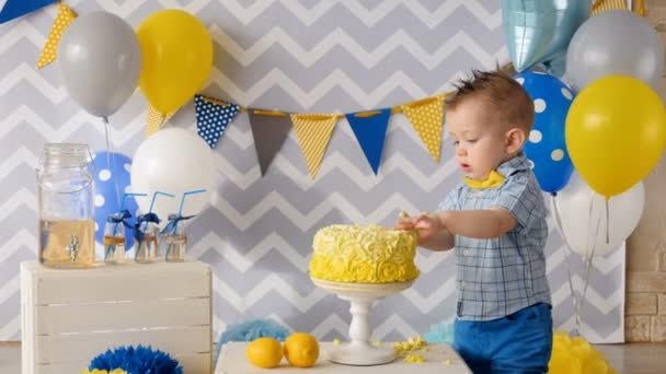 A birthday boy destroys a cake with his hands.