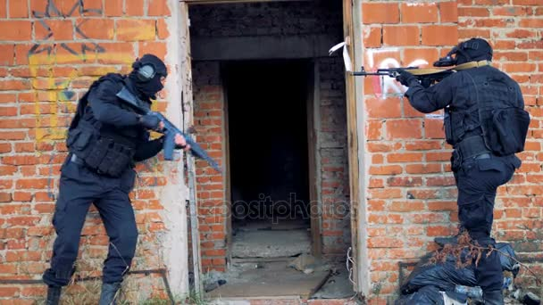 Two well armed soldiers enter an old buildings during hostage release.