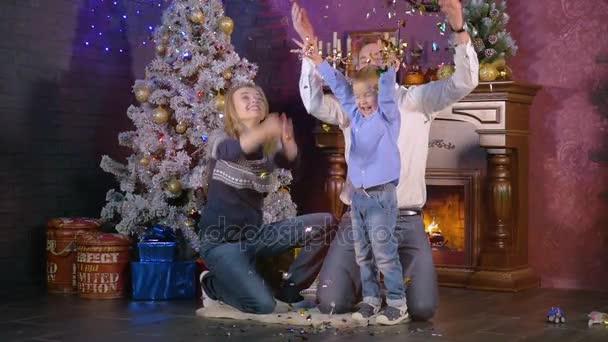 Šťastná rodina vánoční krbu Házejte konfety. Zpomalený pohyb.