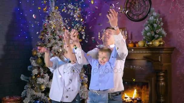 Giovane famiglia felice gioiosa madre, padre e figlio che hanno divertimento al camino di Natale.