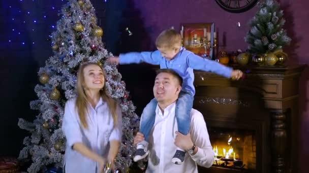 Madre di famiglia gioiosa, padre e figlio che hanno divertimento al camino di Natale. Close-up.