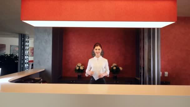 Krásny usmívá a dávat klíče kartu v hotelové hale