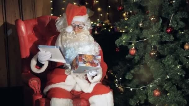 Santa Claus balení Dárkový box sedí v křesle u vánočního stromu.