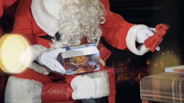 Mikulás játék helyezett egy ajándékdobozt karácsonyfa. 4k.