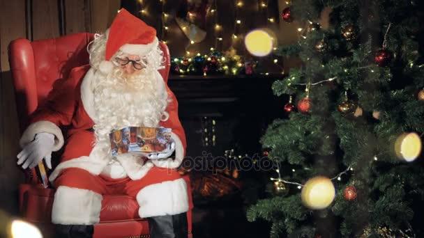 Santa připravuje dárky u vánočního stromu. 4k.