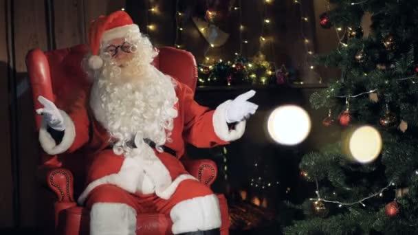 Veselý Santa Claus ukázal na vánoční krb.