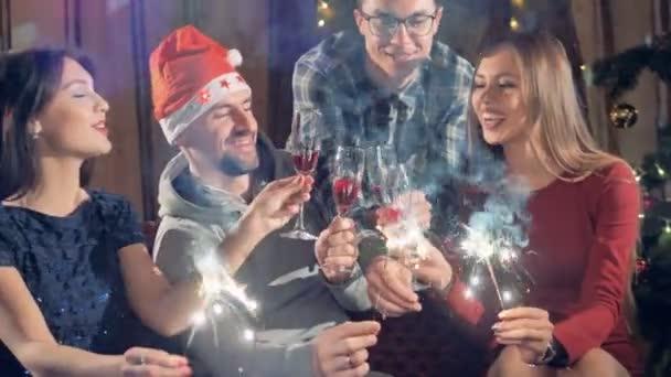 Boldog vidám baráti társaság, az új év karácsonyi party világítás csillagszórók szórakozás mosolyogva ünnepli Szilveszter. 4k