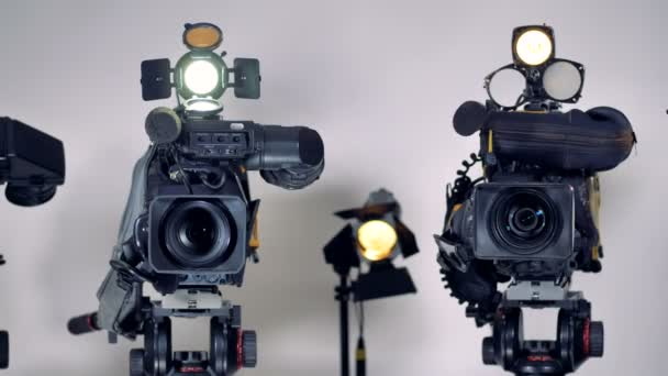 A close view on video cameras lenses and mikes.
