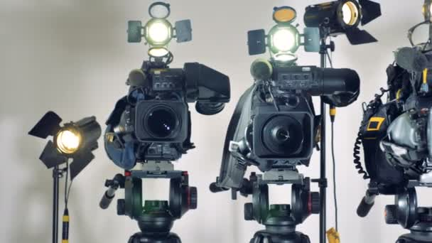 Several video cameras with working lights.