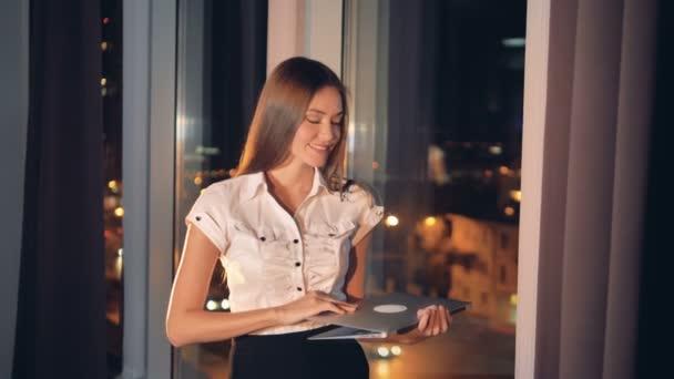Obchodní žena usměje a zavře její laptop
