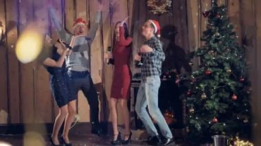 Four friends dance and sing near a Christmas tree.