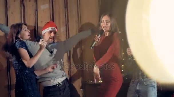 Két párok élvezni Szenteste félnek táncol és énekel együtt.