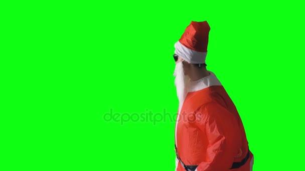 Santa Claus poukazuje na skrytý objekt na zeleném pozadí