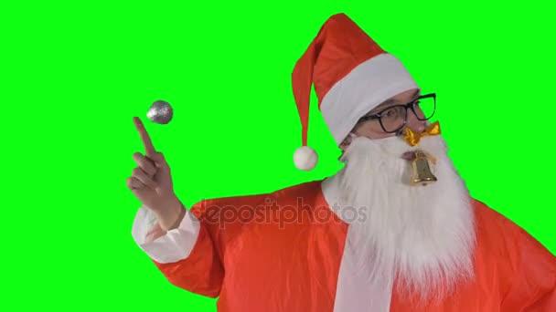 Santa Claus na zeleném pozadí hraje s vánoční ozdoby