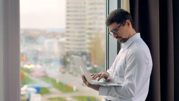 Zamyšlený podnikatel používá notebook u okna.