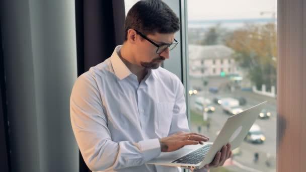 Podnikatel typy na notebook se dvěma prsty.