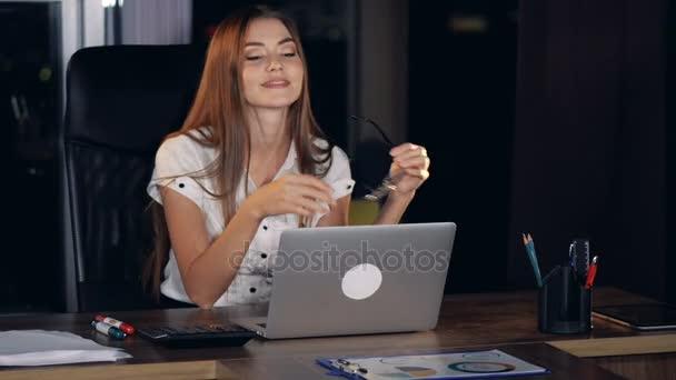 Podnikatelka sundá brýle na laptop.