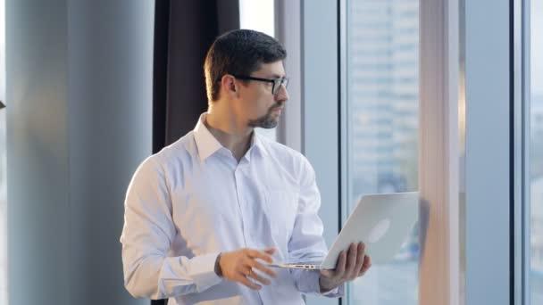 Zaneprázdněný podnikatel typy na laptop s prsty jedné ruky.