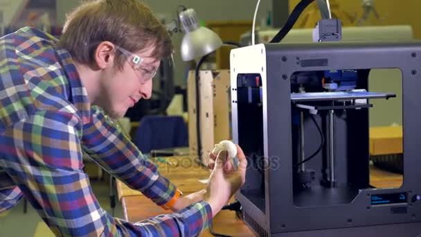 Ein glücklicher Ingenieur hält einen weißen Prototyp-Kopf in der Hand und blickt auf einen funktionierenden 3D-Drucker. 4k.