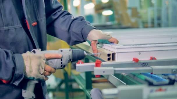 Pracovník výroby plastových oken. Montážní linka Pvc oken a dveří