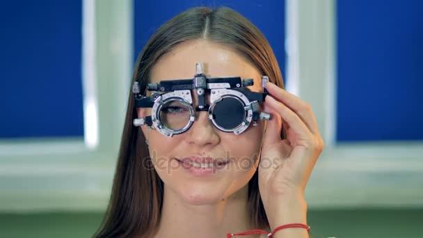 Mladá žena během zkoušku zraku na sobě zkušební snímky.