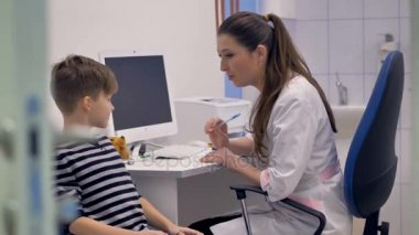 Friendly doctor writes prescription for young boy.