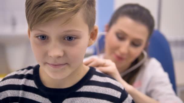 Ein Arzt hört einer Schülerin mit einem Stethoskop zu. 4k.