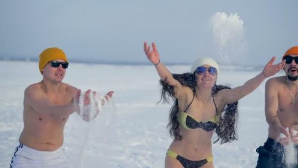 Tři přátelé na sobě plavání zavře hrát s sníh