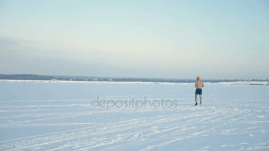 A man in athletic shorts jogs on a wide snowy field.