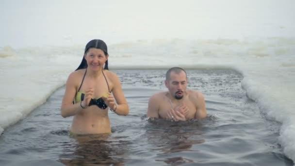 Muž a žena v plavání obleky v díře v ledu
