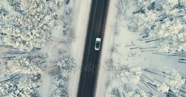 Auto fährt auf von Schnee gereinigter Landstraße.