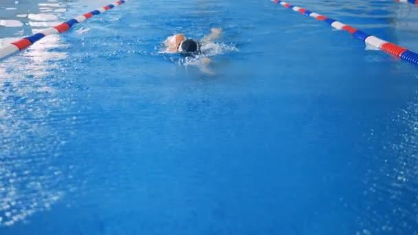 Plavec v pomalém pohybu zpět procházení stěhování do fotoaparátu.