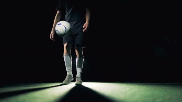 Fotbalista je žonglování a drží míč na levou nohu, čelní pohled.