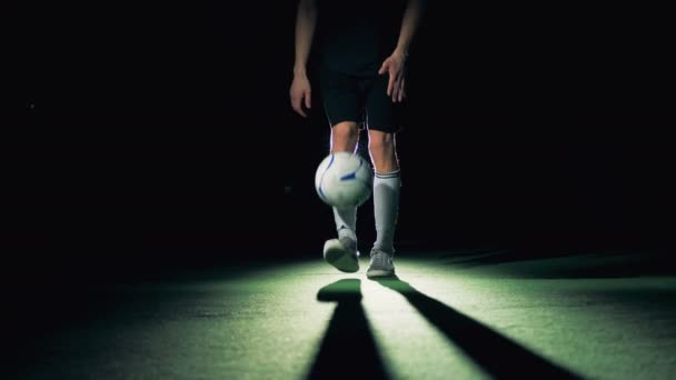 Professional soccer player is tossing and making around the world trick, front view.