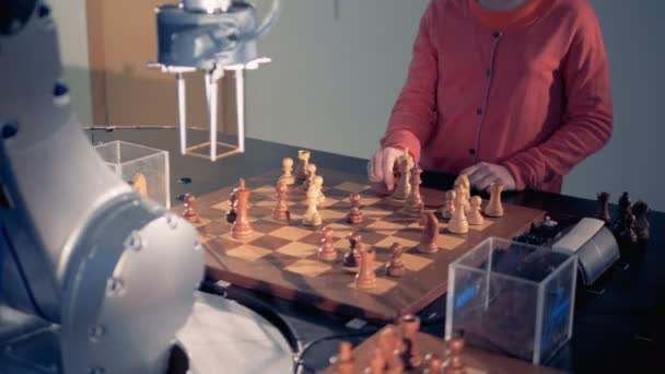 A robotic arm and a little girl are rearranging chess pieces