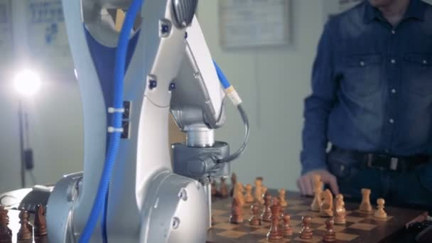 An adult man and a robot are playing chess and capturing each others pieces
